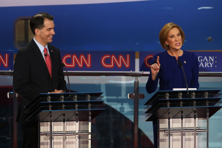 Republican presidential candidate Wisconsin Gov. Scott Walker (L) looks on as Carly Fiorina speaks during the presidential debates at the Reagan Library on September 16, 2015 in Simi Valley, California. Fifteen Republican presidential candidates are participating in the second set of Republican presidential debates.  (Photo by Justin Sullivan, Getty Images)