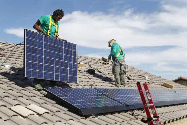 The SolarCity workers install rooftop panels. (Source: Las Vegas Review-Journal)