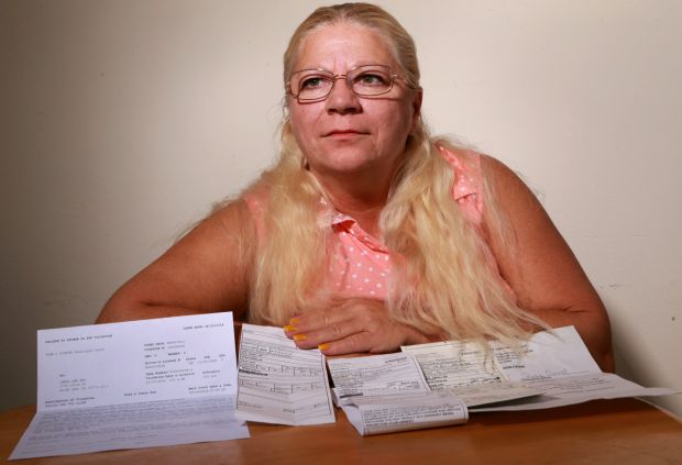 Carol Ray, of south St. Louis County, poses with two unpaid tickets, a warning and a failure to appear/pay notice from two municipalities on Friday, Sept. 19, 2014. She says she cannot afford to pay them, and she has skipped court dates for each of them for fear of being arrested. (Photo from St. Louis Post-Dispatch)